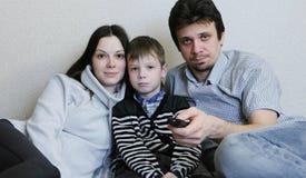 hålla ögonen på för tv Den unga den familjmamman, farsan och sonen håller ögonen på TV tillsammans Farsaströmbrytarekanaler Arkivfoto