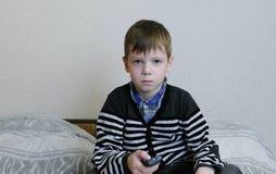 hålla ögonen på för tv Den uttråkade pojken håller ögonen på TV och kopplar kanalerna Arkivbilder