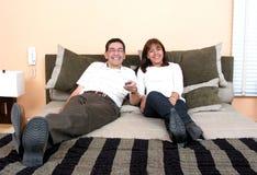 hålla ögonen på för tv för par lyckligt avslappnande Arkivbild