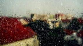 Hålla ögonen på regnet till och med det oskarpa exponeringsglaset av ett fönster arkivfilmer
