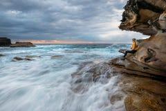 Hålla ögonen på vågorna flyga iväg, precis som liv från havsgrottan arkivbild