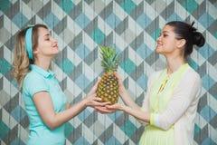 Hållananas för två härlig kvinnor tillsammans Arkivfoton
