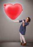 Hållande älskvärd röd hjärta 3d för ung lady Fotografering för Bildbyråer