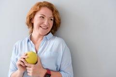 Hållande äpple för angenäm förtjust kvinna royaltyfri foto