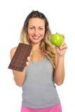 Hållande äpple- och chokladstång för attraktiv kvinna i sund söt skräpmatfrestelse för frukt kontra Arkivfoto