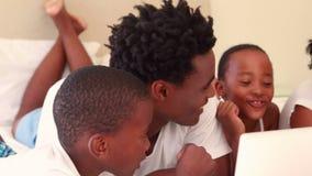 Hållande ögonen på dator för lycklig familj stock video