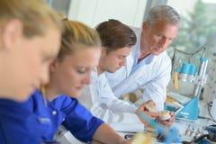 Hållande ögonen på deltagare i utbildning för arbetsledare i tand- laboratorium arkivbild