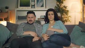 Hållande ögonen på drama för make och för fru på TV med ledsna framsidor som sitter på soffan i hus lager videofilmer