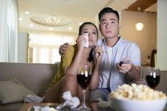 Hållande ögonen på dramafilm för par hemma fotografering för bildbyråer