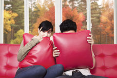 Hållande ögonen på fasafilm för par på tv Royaltyfri Foto