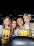 Hållande ögonen på film för förvånad familj i teater Arkivfoto