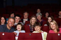 Hållande ögonen på film för familj i bio royaltyfri fotografi