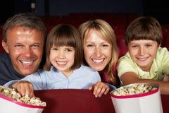 Hållande ögonen på film för familj i bio fotografering för bildbyråer