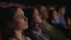 Hållande ögonen på film för flicka på bion Flickasammanträde i teater och hållande ögonen på kapacitet lager videofilmer