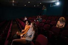 Hållande ögonen på film för grupp människor arkivfoton
