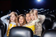 Hållande ögonen på film för häpen familj i bioteater Arkivfoto