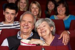 Hållande ögonen på film för höga par i bio Royaltyfri Foto
