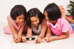 Hållande ögonen på film för liten asiatisk flicka på mobiltelefonen Arkivbild