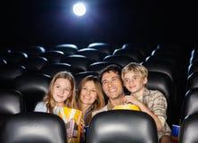 Hållande ögonen på film för lycklig familj i teater Arkivbilder