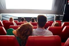 Hållande ögonen på film för lyckliga par i teater eller bio arkivbild