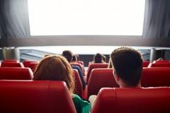 Hållande ögonen på film för lyckliga par i teater eller bio Royaltyfri Bild