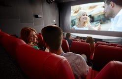 Hållande ögonen på film för lyckliga par och samtal i teater Royaltyfri Fotografi