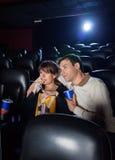 Hållande ögonen på film för par i bioteater arkivfoto