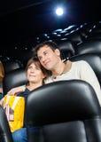 Hållande ögonen på film för tillgivna par i teater Fotografering för Bildbyråer