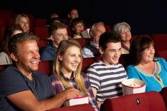 Hållande ögonen på film för tonårs- familj i bio Royaltyfri Fotografi
