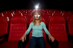 Hållande ögonen på film för ung kvinna i teatern 3d Royaltyfri Bild