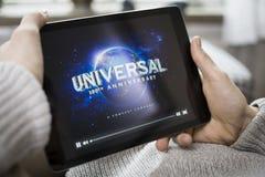 Hållande ögonen på film på iPad. Universal Pictures Royaltyfri Foto