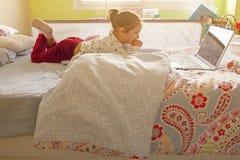 Hållande ögonen på filmer för liten flicka med en bärbar dator Arkivfoton