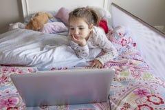 Hållande ögonen på filmer för liten flicka med en bärbar dator i säng Arkivbild