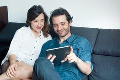 Hållande ögonen på filmer för lyckliga par på den digitala minnestavlan Royaltyfria Bilder