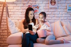 Hållande ögonen på filmer för moder och för dotter på telefonen som hemma äter popcorn på natten royaltyfri bild