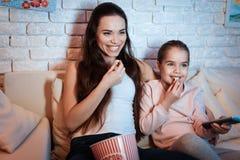Hållande ögonen på filmer för moder och för dotter på television på natten hemma arkivfoton