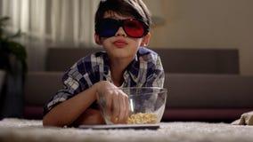 Hållande ögonen på filmer för pys i exponeringsglas 3d och ätapopcorn som hemma tycker om royaltyfria bilder