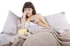 Hållande ögonen på filmer i säng royaltyfri bild
