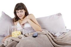 Hållande ögonen på filmer i säng Royaltyfri Fotografi