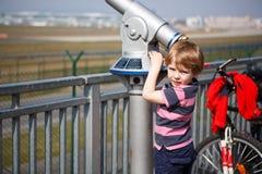 Hållande ögonen på flygplan för liten blond pojke i observationsrör på airpo Royaltyfri Bild