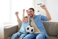 Hållande ögonen på fotboll för fader och för son på tv hemma Royaltyfria Foton