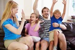 Hållande ögonen på fotboll för familj på TV som firar mål royaltyfri fotografi
