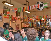 Hållande ögonen på fotboll för folk i en restaurangstång arkivbild
