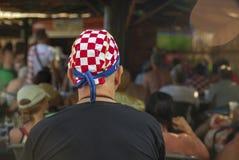 Hållande ögonen på fotboll för gammal kroatisk fan på TV royaltyfria bilder