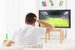 Hållande ögonen på fotboll för man och drickaöl hemma Royaltyfri Foto