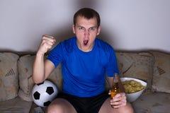 Hållande ögonen på fotboll för rolig man på tv Royaltyfri Fotografi