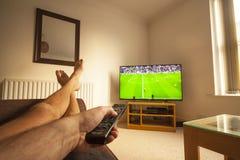 Hållande ögonen på fotboll på TV:N Royaltyfria Foton