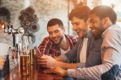 Hållande ögonen på fotboll på Smartphone och att dricka öl i stång royaltyfri bild