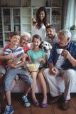 Hållande ögonen på fotbollsmatch för lycklig mång--utveckling familj på television i vardagsrum arkivfoto