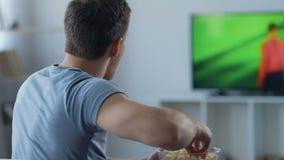 Hållande ögonen på fotbollsmatch för nervös fan framme av TV och att göra en gest och äta popcorn lager videofilmer